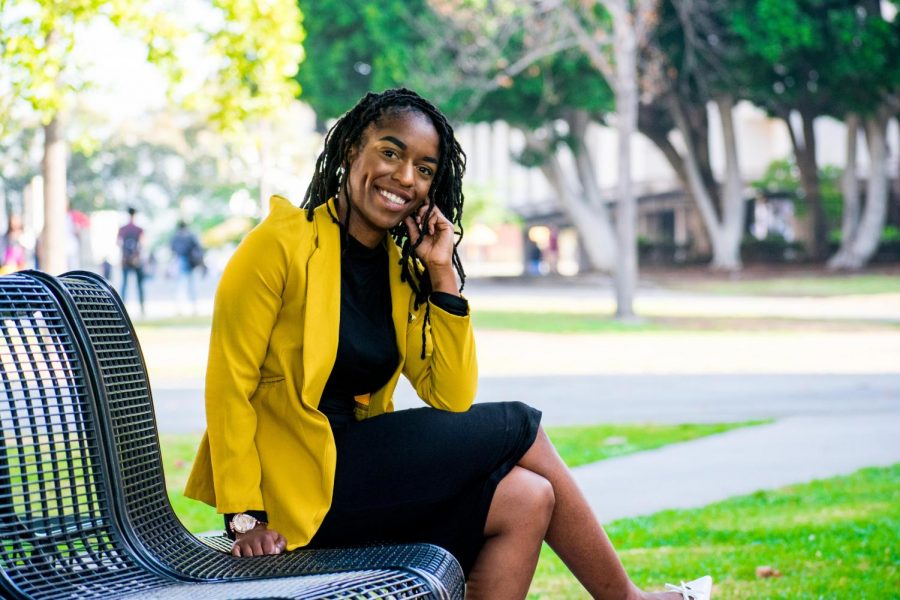 ASI+President%2C+Nia+Johnson%2C+is+smiling+and+sitting+on+a+campus+bench+with+her+mustard+jacket%2C+posing+with+her+hand+to+her+cheek