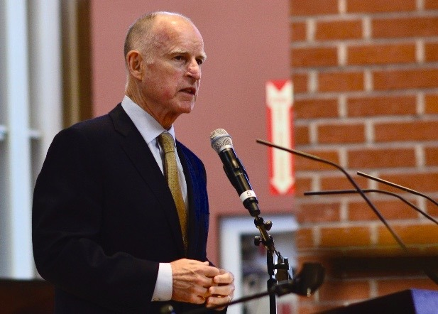 Jerry Brown, governor of the state of California is speaking in front of a podium