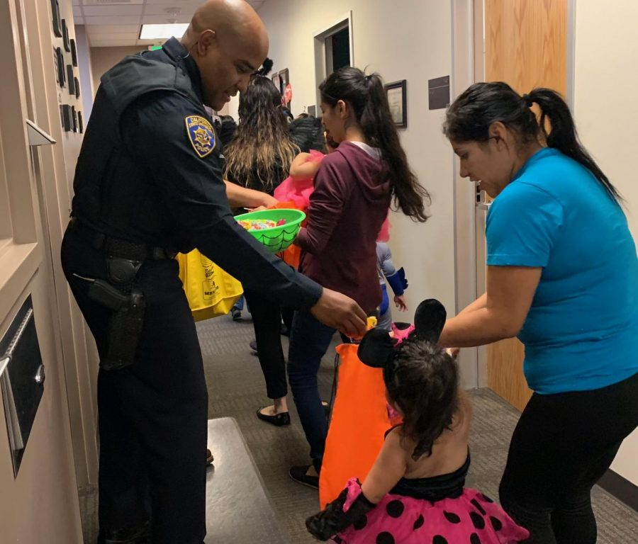 Policemen are handing out candy for the little children in the police department, on Halloween