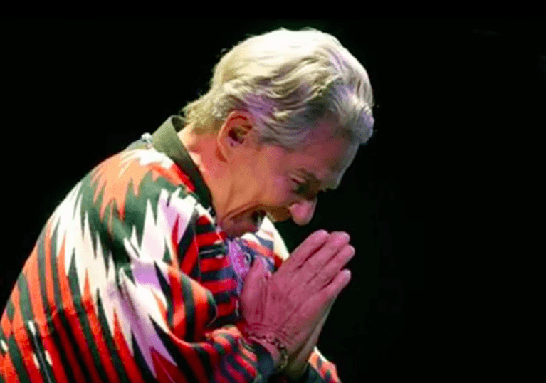 Chavela+Vargas+is+leaning+forward+with+their+hands+pressing+together%2C+making+a+prayer+hand.