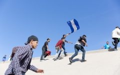 Students walking uphill a concrete hill, holding a blue flag.