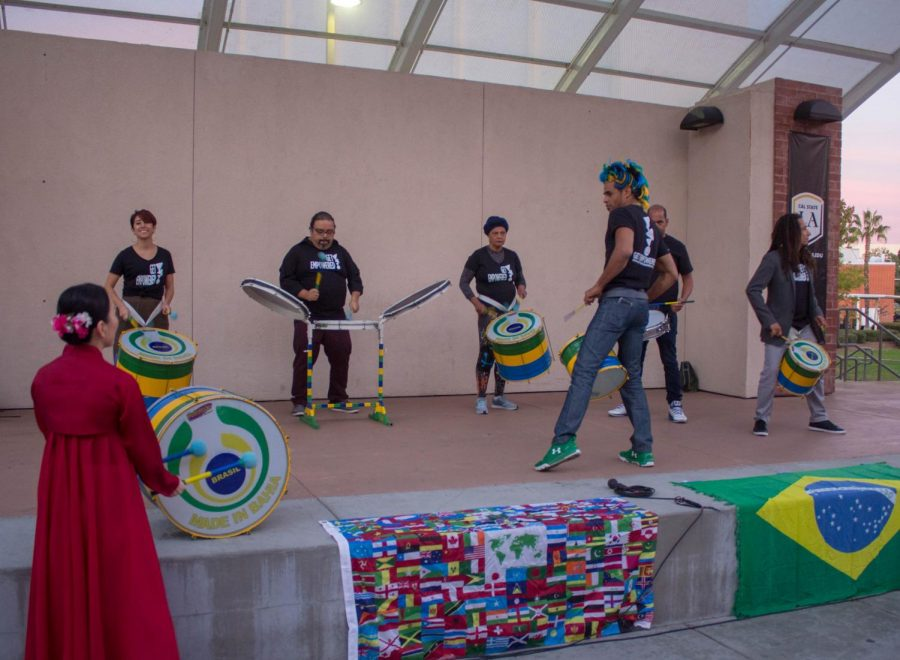 A group is is singing while holding a drum kit in Cal State LA