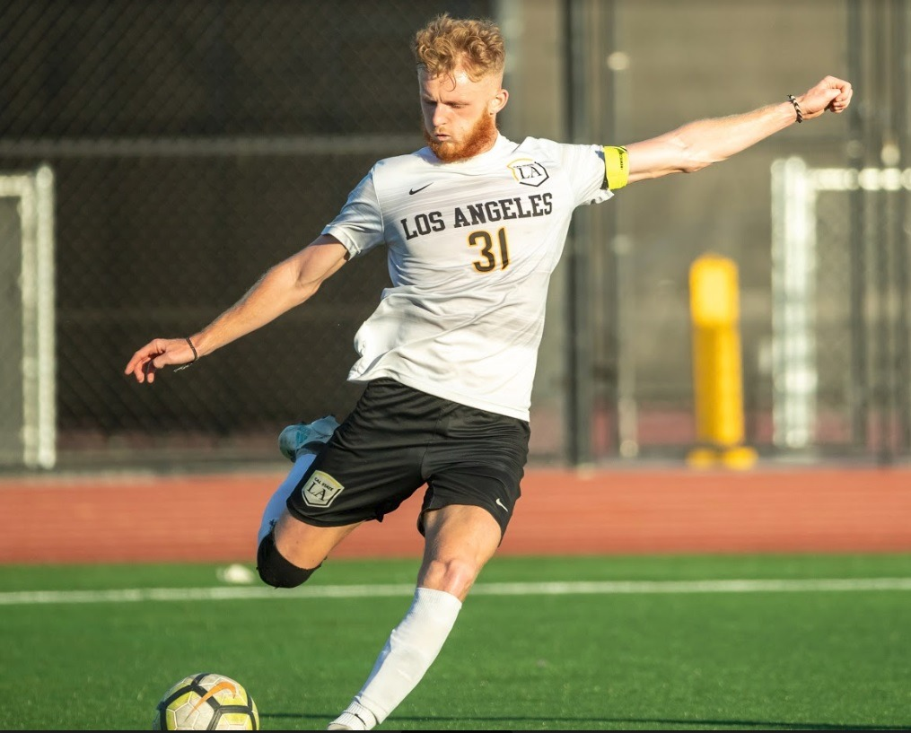 Golden Eagle midfielder, Samuel Croucher, a graduate student, crosses the ball at Cal State LA's home field.
