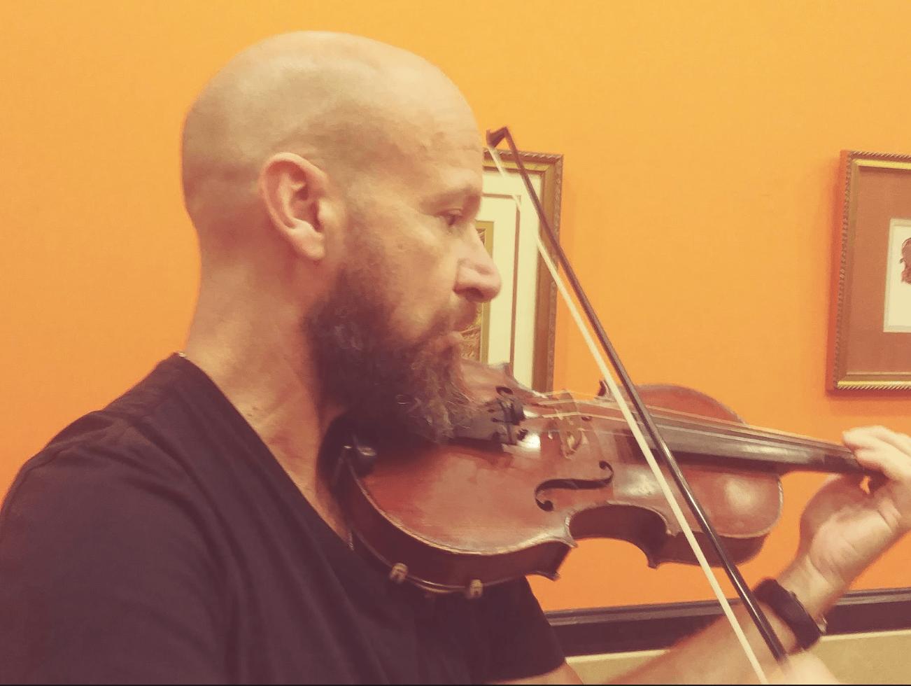 Timothy Maloof playing the violin. (Boushra Rafi/UT)