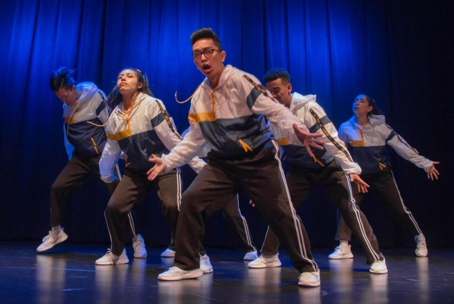 A group of hip hop dancers, in white and blue jumpsuits, are posing for their cool looking picture