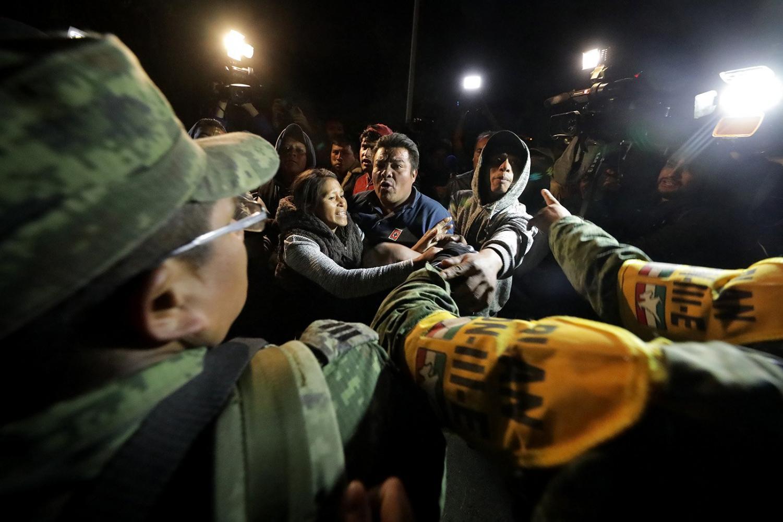 Los aldeanos discuten con los militares despues de la explosion del ducto, pertenciente a PEMEX, para buscar a sus familiares cerca del area. Foto por Tribune News Service