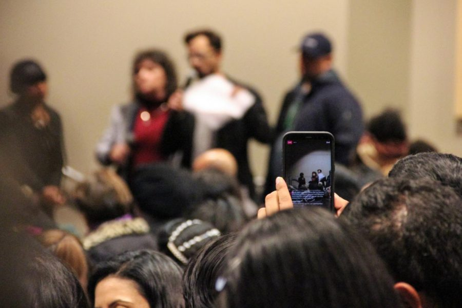 While attending the Impaction Proposal Hearing located at Cal State LAs U-SU Theater, an audience member live streams the event on their smart phone.