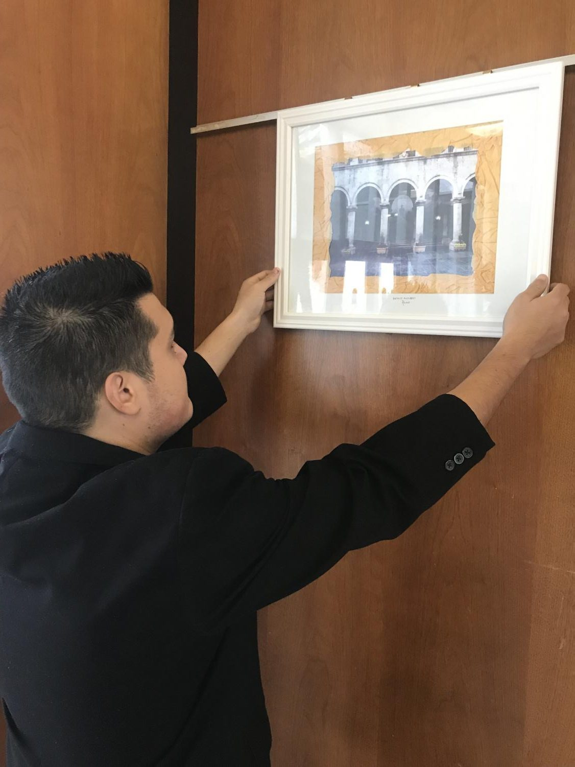 Basilio Alonzo hangs up his artwork at Alhambra city hall. (Daniel  Lindley/Community News)