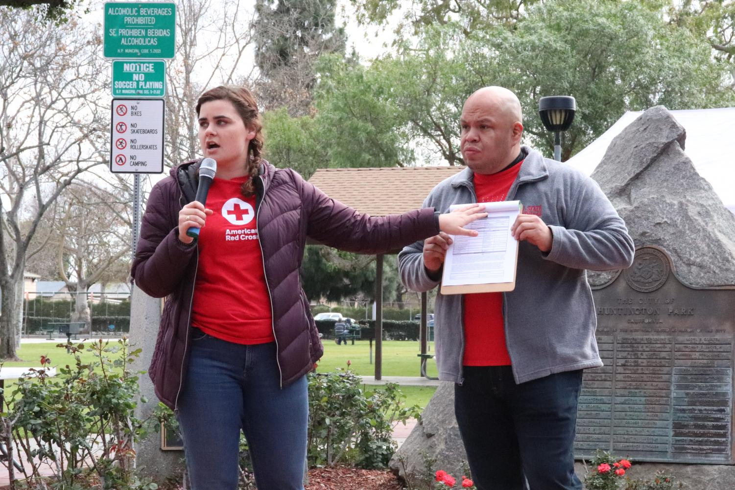 Lydia Hoffman (left) and Nelson Cox (right) instruct volunteers before they install fire alarms in homes. Photo by Joshua Letona.