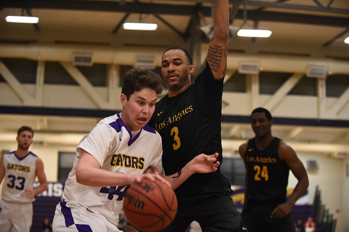 Golden Eagles forward, number 3, Jihad Woods (right) defends the Gators' number 44, center Ryne Williams (left) during the opening round of the 2019 CCAA tournament at San Francisco State University's Main Gym at Don Nasser Plaza. Photo courtesy of San Francisco State Athletics Department.