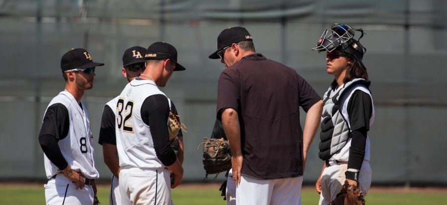 Alex DeAngelis, assistant coach, calls the Golden Eagles to a meeting on the mound.