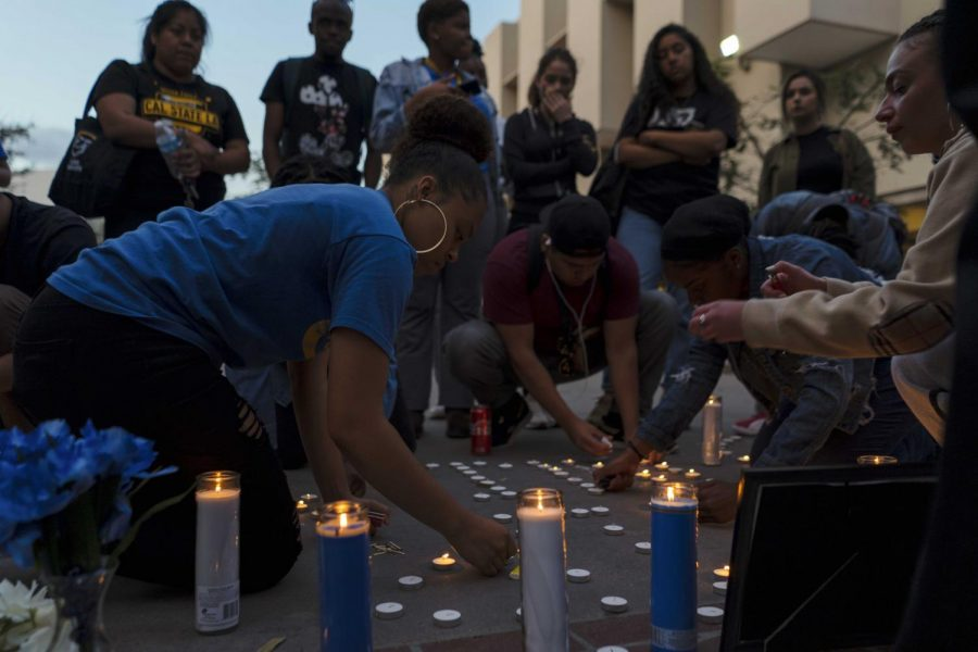 Students begin gathering as the candles are lit to pay respect and honor rapper Nipsey Hussle last Thursday at the Golden Eagle Statue. Cal State L.A., 2019.