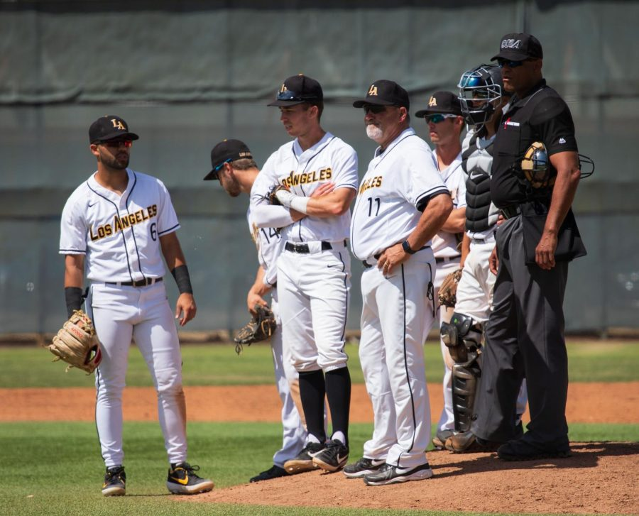 The Golden Eagles strategize during a pitching change.   Pictured left to right: Third baseman (6) Nate Alam, shortstop (14) Tyler Odekirk, first baseman (9) Spencer Sundahl, head coach Vince Beringhele (11), second baseman (8), Jordan Peabody and catcher (15) Noe Garcia.