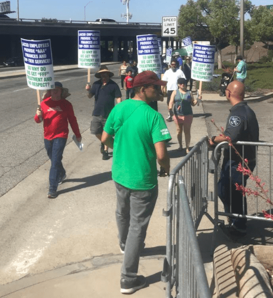Sanitation workers protest in front of the street, in front of a security guard. (Courtesy of AFSCME District Council 36.)