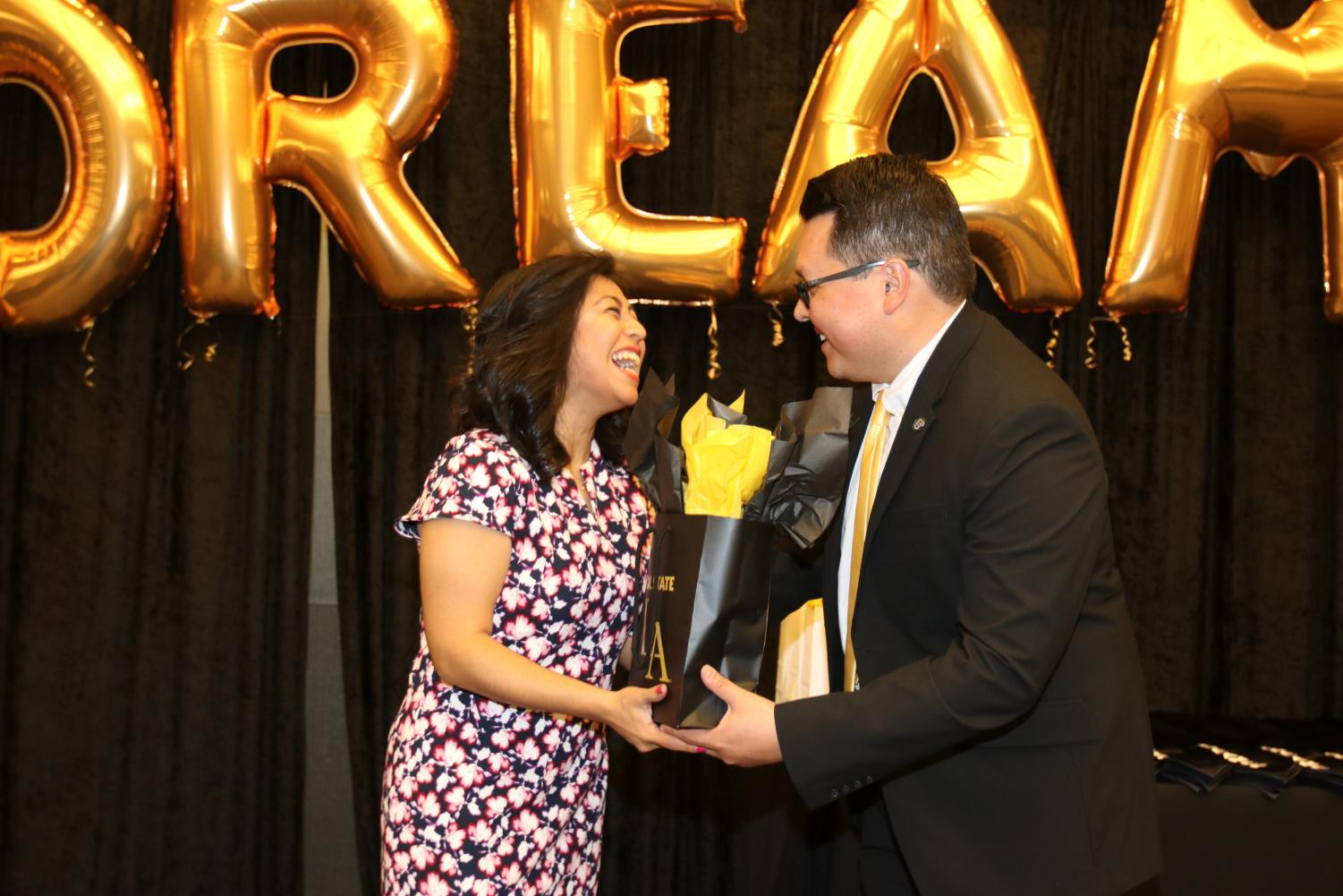 Henoc Preciado (Director of the Erika J. Glazer Family Dreamers Resource Center), providing Keynote Speaker Cristina Jimenez a thank you gift after she delivered her speech.