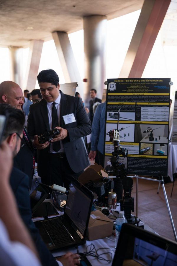 Justin Torres shows an attendee his team's project on a robotic tool dock.