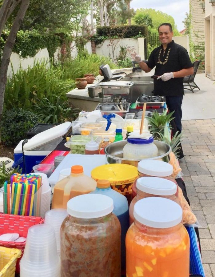 A portrait of Oscar Hernandez catering a party with items such as tacos, corn and fruit.