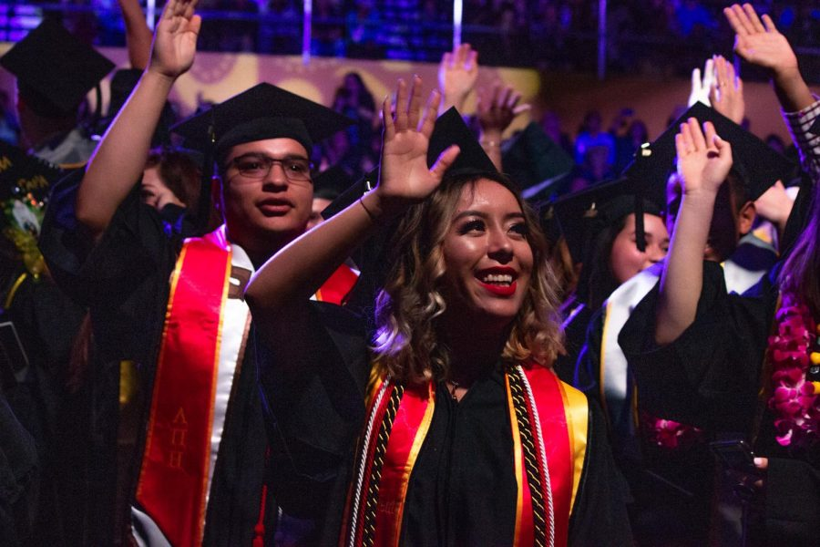 Graduates of Cal State Los Angeles's Arts and Letter Department wave to their family, friends, and supporters during the 2019 Cal State LA Commencement