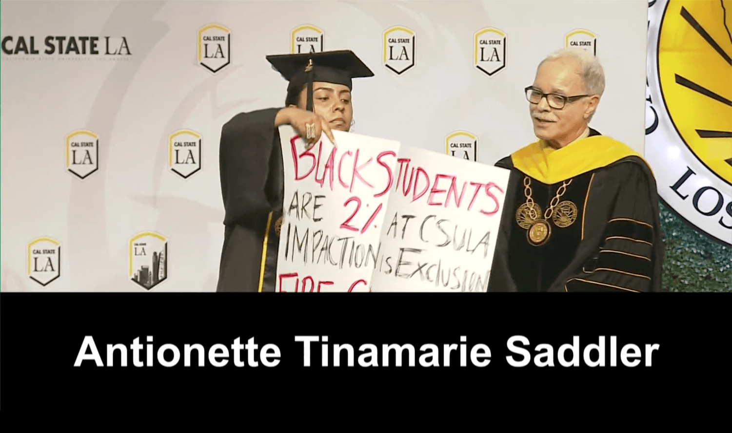 Screen shot of Cal State LA's live streamed video of the college of Natural and Social Sciences. Antoinette Tinamarie Saddler, a Cal State LA Pan-African Studies graduate, protests Presidetn William A. Covino by holding up a sign that reads