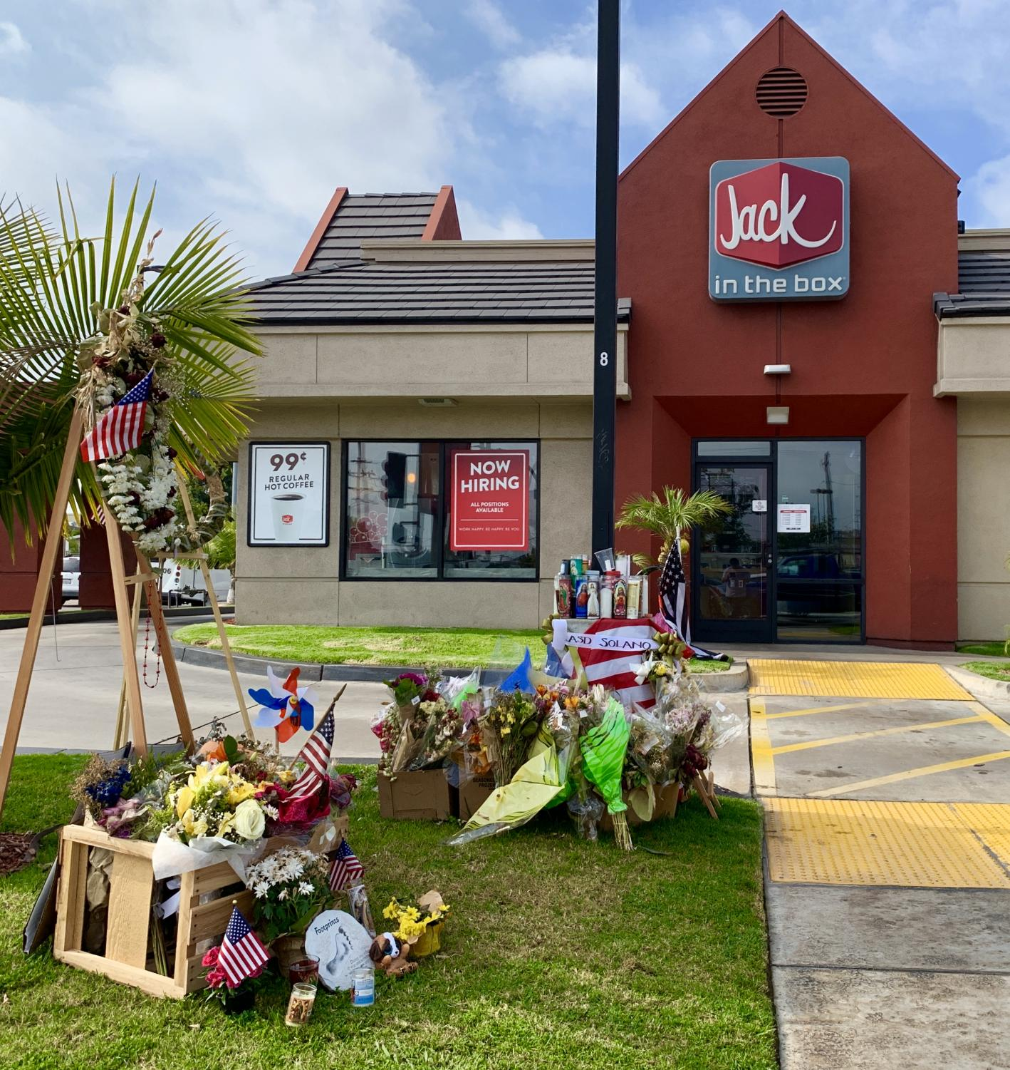 A memorial site for LA County deputy, Joseph Gilbert Solano, is placed at the entrance of the Alhambra Jack in the Box where the shooting occurred