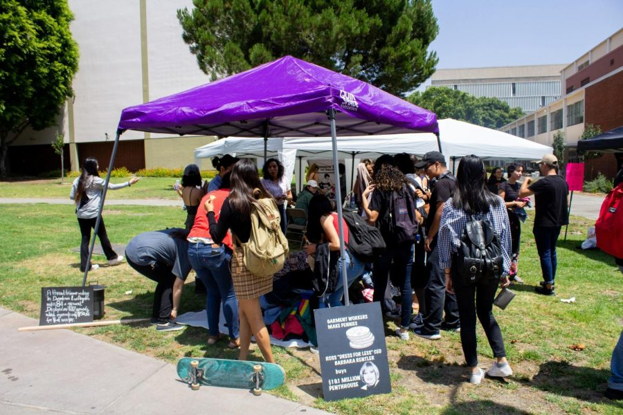 Cal State LA students gather around a pile of 632 clothes, in the Cal State LA campus
