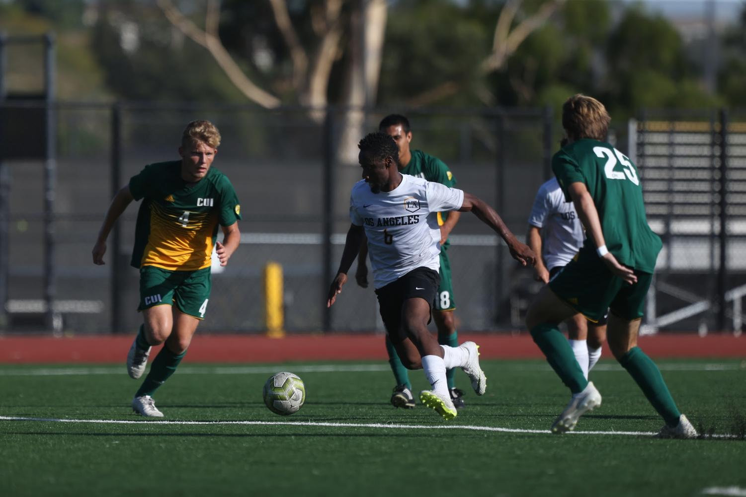 Cal State LA forward Cyrille Njomo (center) fights to keep possession of the ball against the Concordia Irvine eagles.
