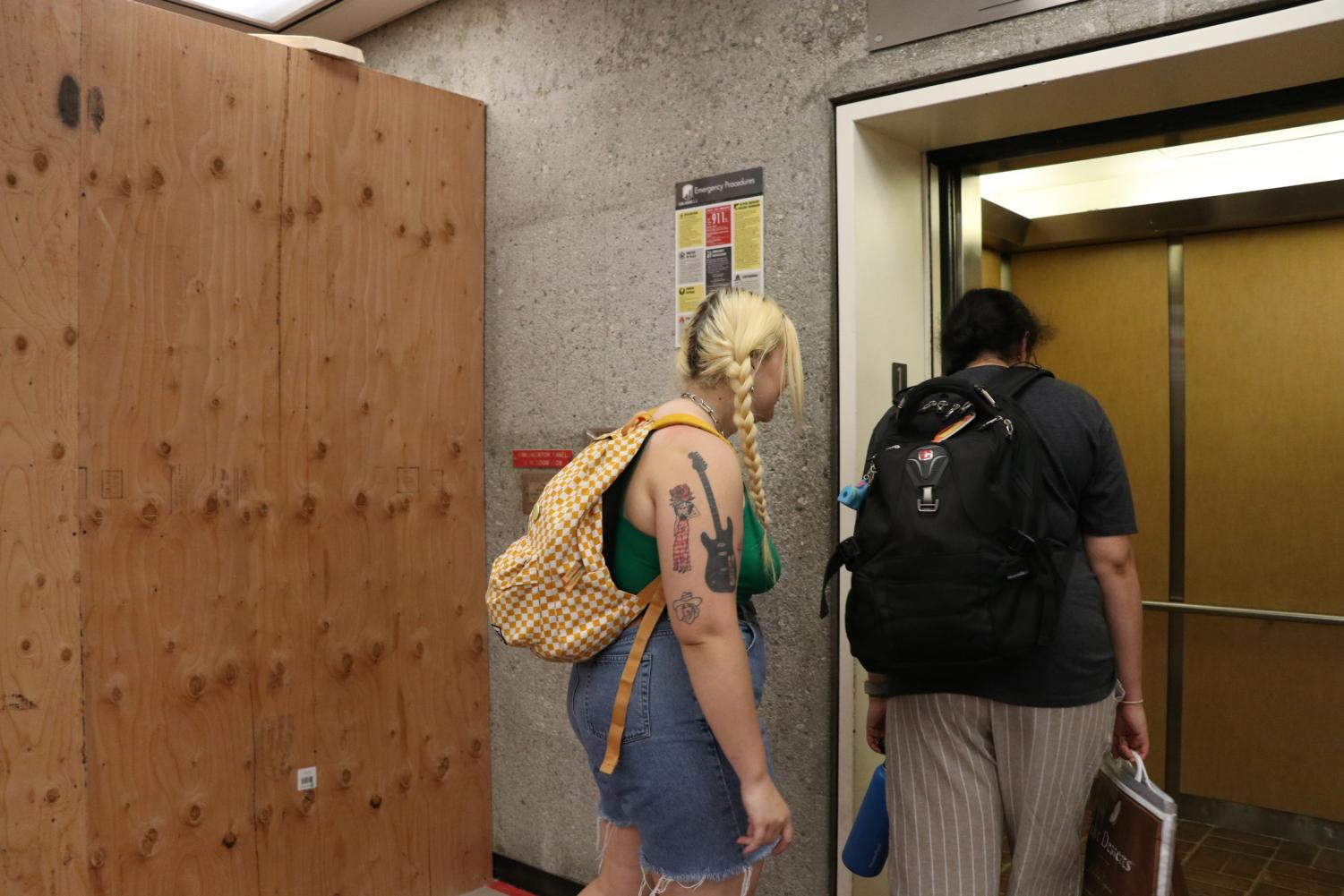 Zoe Little (left), and Abhiravi Charathram (right), board the second elevator in the North library due to ongoing maintenance of the other library elevator.