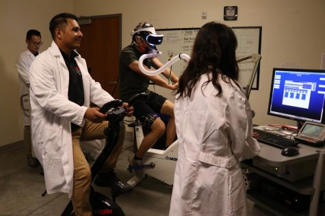 Axel Munoz (left) follows along with the movements of the research participant as he goes through a virtual reality bike ride.