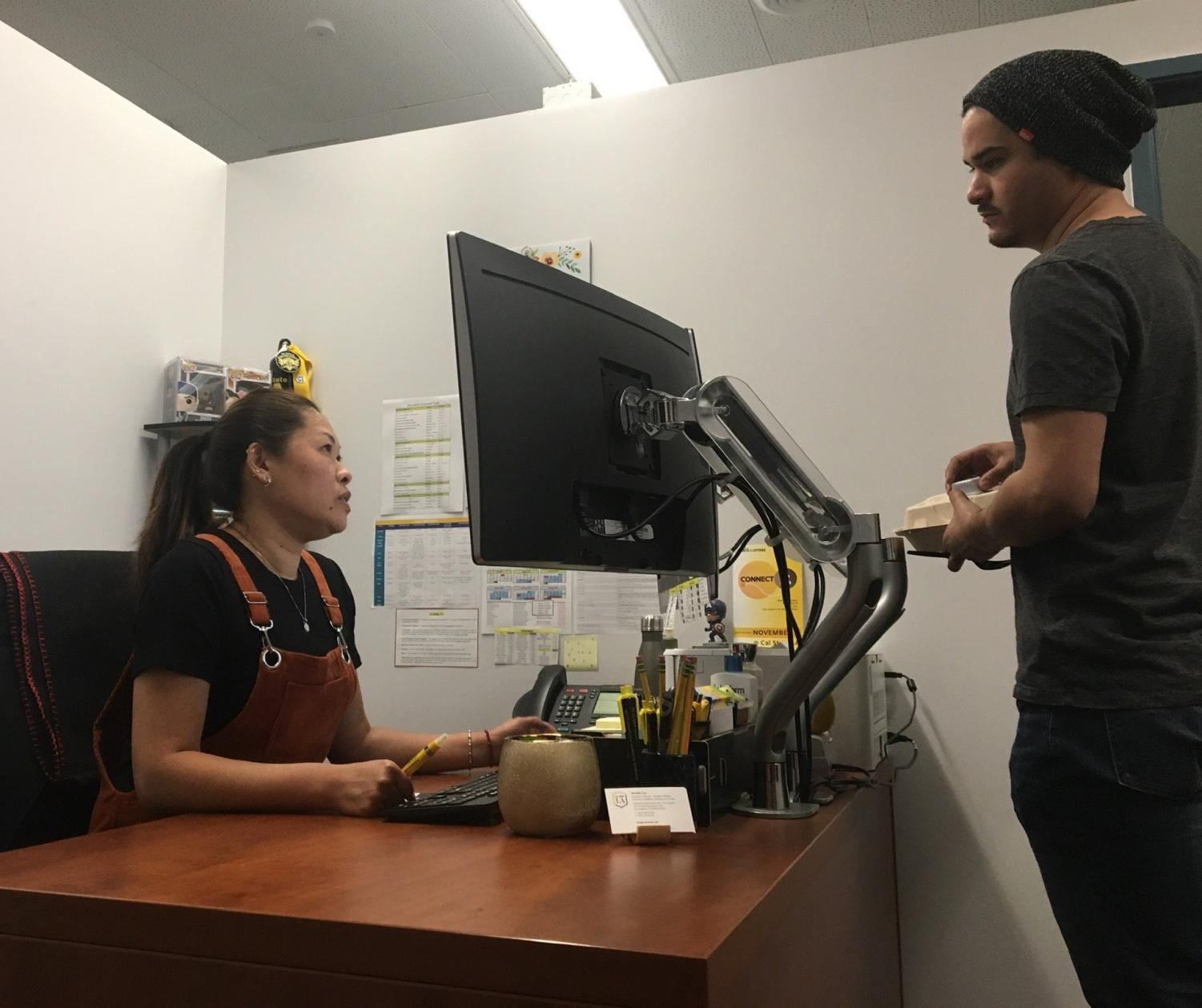 Advisor Jennifer Luo and front desk support Johnny Benitez discuss the appointment schedule.
