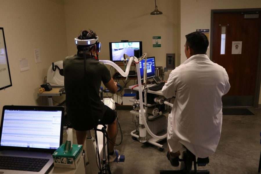 A student participating in the Cal State LA Kinesiology lab virtual reality exercise research rides a bike in VR, being able to race others on screen and feel like they are going up hills.