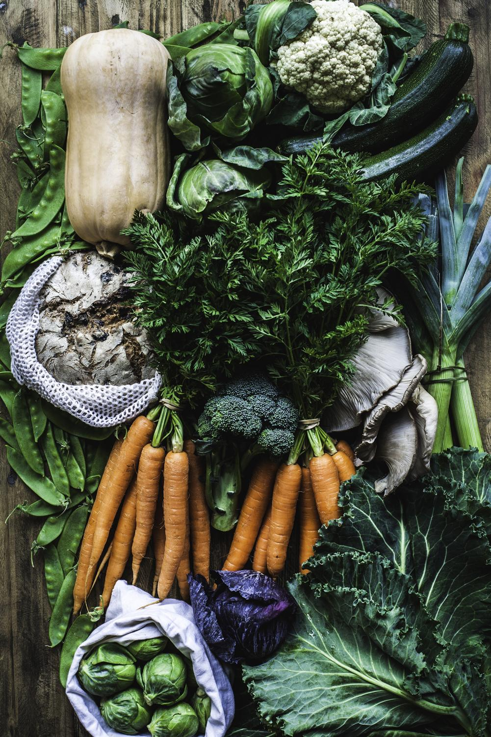 Fresh vegetables, mushrooms, and bread are shown on a flatlay ready for the farmer's market.