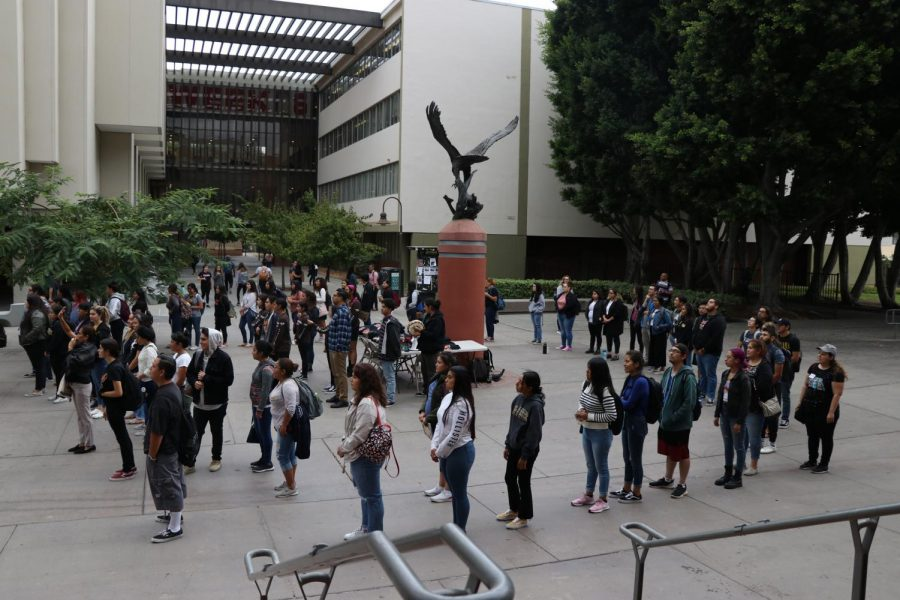 Those attending the Brown Issues pop-up circle the Eagle statue to honor the Tongva people and the land that Cal State LA sits on.