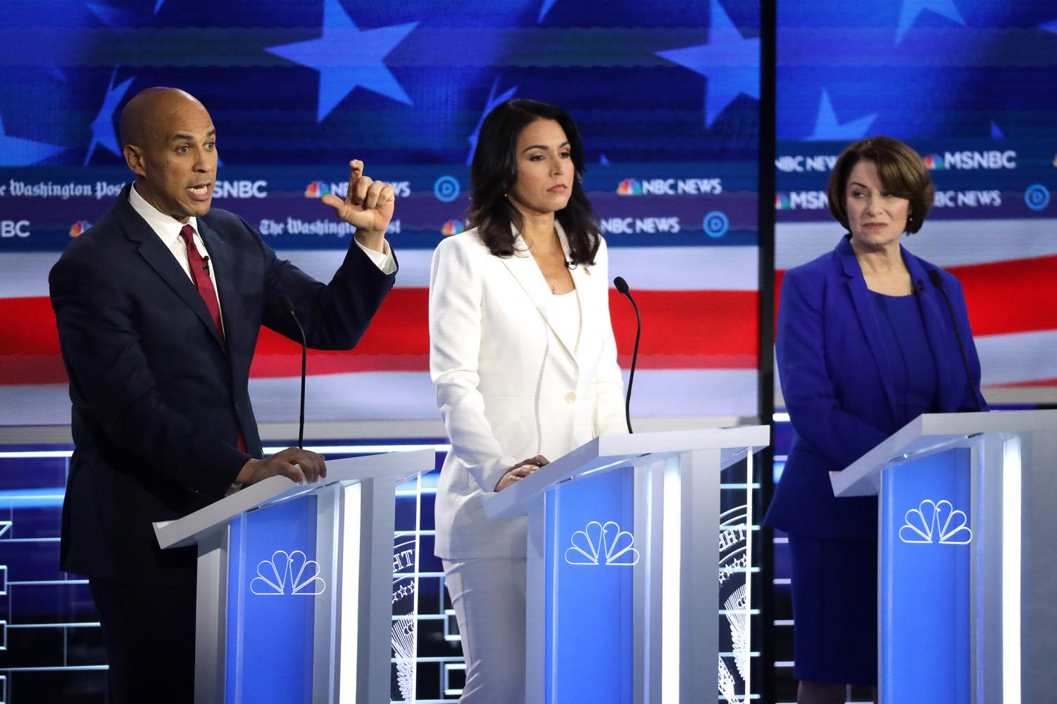 Democratic presidential nominees, Cory Booker (left), Tulsi Gabbard (middle), and Amy Klobuchar (right), at the Democratic Presidential Debate on November 20, 2019.