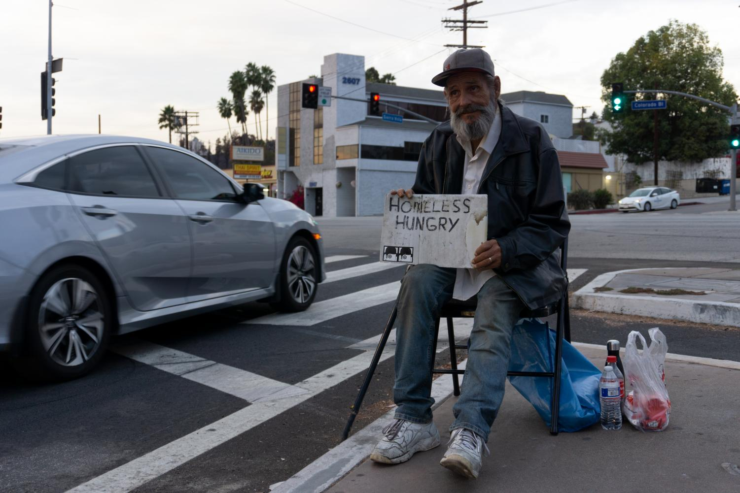 Larry McCarter, who says he's been homeless for 10 years, sits on Sierra Villa Drive and Colorado Boulevard, asking for donations.