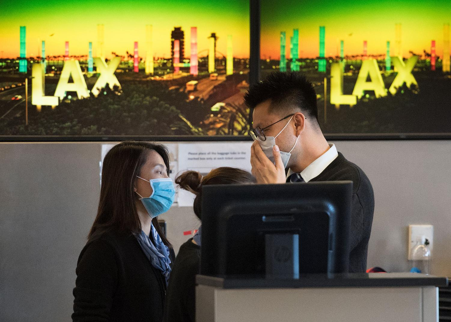 Airline check-in staff at LAX airport wear a face mask to protect themselves from the coronavirus.