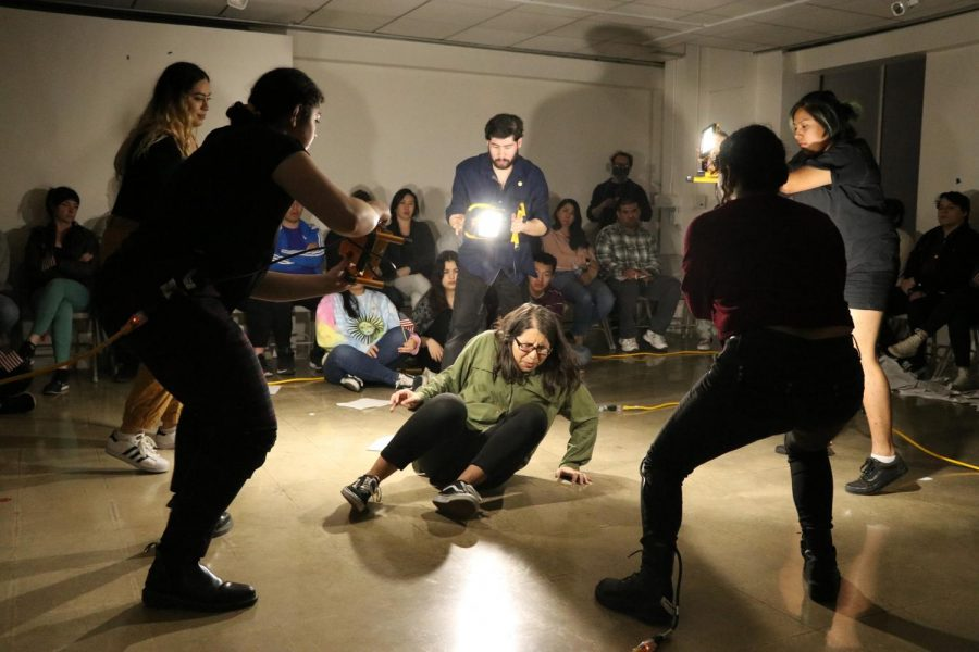 Los estudiantes actúan en la producción de Soñando de Nuestro Futuro. En el campus encienden sus luces mientras hostigan a una actriz que interpreta el papel de una receptora de DACA.