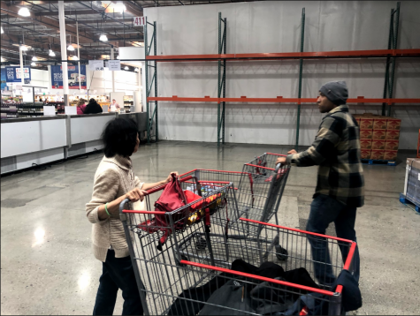 Shoppers walk past empty shelves at Costco. By Vanessa Wyatt.