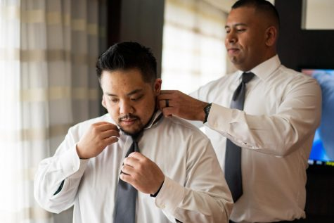 Christopher Lazaro is shown dressed up and having his tie adjusted before a party.