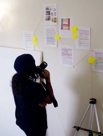 Maryse Bombito looks at papers with notes taped to a wall as she organizes her Healing Through Art project.