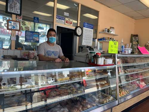 Arturo Nunez, a small business owner, stands behind the counter at his shop while wearing a mask.