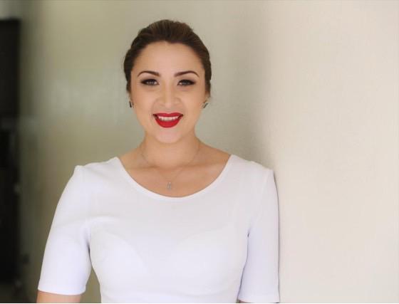 Headshot of Denise Diaz, donning a white shirt and bright red lipstick. Courtesy of Denise Diaz.