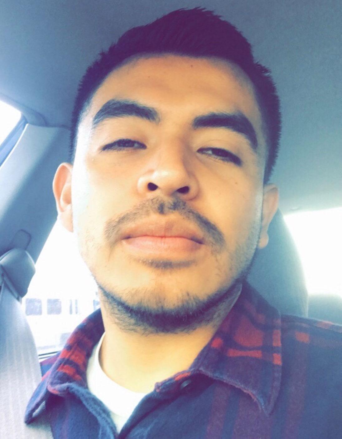 Headshot of Elias Garcia in the car wearing a plaid shirt.
