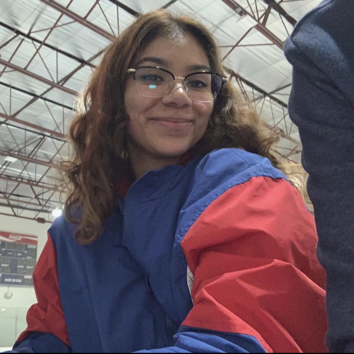 Headshot of Isela Rodriguez, who has glasses and is wearing a blue and red jacket. Courtesy of Isela Rodriguez.