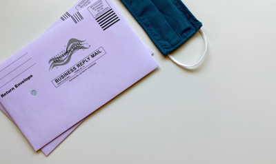 An envelope to vote by mail and a mask.