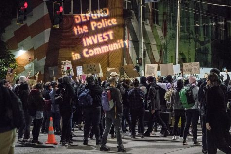 Protestors gathered at night time with text projected on a wall that says,