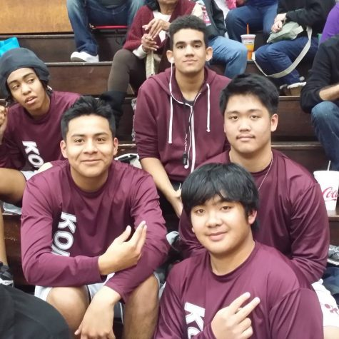 Jericho Dancel and his wrestling teammates sit on some bleachers wearing maroon uniforms.