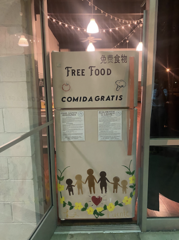 "A fridge in the doorway. It reads ""free food"" on it and has decals on it of children holding hands."