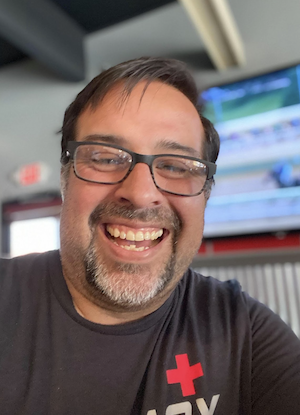 A headshot of Jaime Brown with glasses and a goatie, smiling.