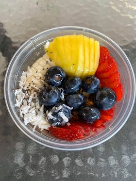 A shot of a bowl of fruit and acai taken from above.