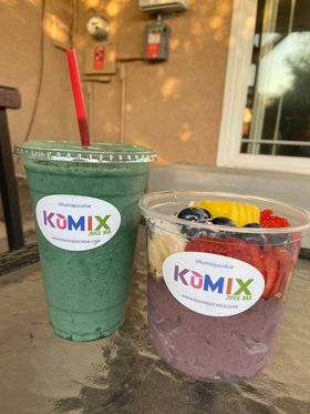 Two clear cups, one with a green smoothie and another with fruit.